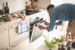Jonge mensen kokend vlees in oven thuis stock afbeelding