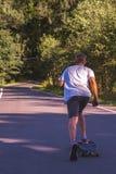 Jonge mensen op de weg met longboard Royalty-vrije Stock Foto's