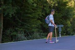 Jonge mensen op de weg met longboard Stock Afbeelding