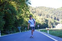 Jonge mensen op de weg met longboard Stock Foto