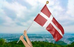 Jonge mensen` s handen die trots de nationale vlag van Denemarken in de hemel, deel het 3D teruggeven golven Stock Fotografie