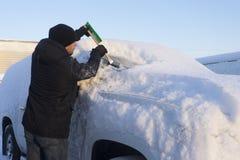 Jonge mensen schoonmakende auto van sneeuw Royalty-vrije Stock Afbeelding