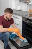 Jonge mensen schoonmakende oven met vod en detergens stock afbeeldingen