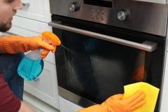 Jonge mensen schoonmakende oven met vod en detergens in keuken stock afbeeldingen