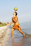 Jonge mensen speelvoetbal op een overzeese kust Royalty-vrije Stock Fotografie