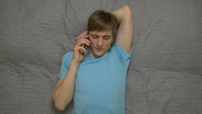 Jonge Mensen Sprekende Telefoon op Bed stock videobeelden