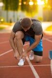 Jonge Mensenagent die zijn schoenen op een renbaan binden Schoenveters, Stedelijke jogger Stock Afbeeldingen