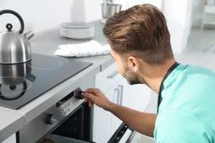 Jonge mensenbaksel iets in oven royalty-vrije stock fotografie