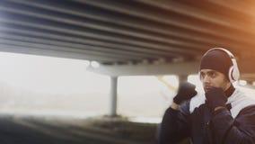 Jonge mensenbokser die in hoofdtelefoons stempels in stedelijke plaats in openlucht in de winter opleiden Royalty-vrije Stock Foto