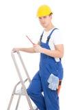 Jonge mensenbouwer in blauwe overtrekken met schroevedraaier op ladder i Royalty-vrije Stock Fotografie