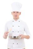 Jonge mensenchef-kok in eenvormige die holdingspan op wit wordt geïsoleerd Stock Foto