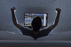 Jonge mensenhuis alleen het letten op voetbal of voetbalspel in televisie die en het vieren doel genieten van royalty-vrije stock foto's