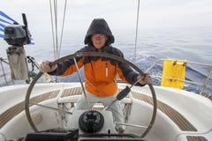 Jonge mensenkapitein in het overzees bij het roer van een varend jacht Sport Royalty-vrije Stock Foto's