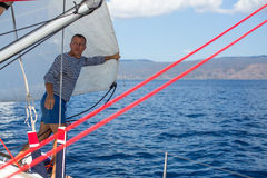 Jonge mensenkapitein - het plaatsen zeilen op de varende jachtboot stock afbeelding