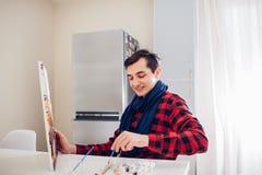 Jonge mensenkunstenaar die thuis het creatieve schilderen schilderen royalty-vrije stock foto
