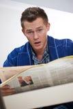 Jonge mensenlezing newspapper stock afbeelding
