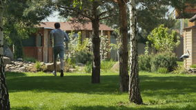 Jonge mensenlooppas door het gazon in de tuin stock videobeelden