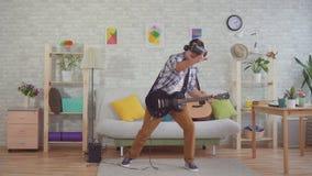 Jonge mensenmusicus in virtuele werkelijkheidsglazen die emotioneel de elektrische gitaar spelen stock videobeelden