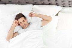 Jonge mensenontwaken in bed met hoofdkussens royalty-vrije stock afbeeldingen