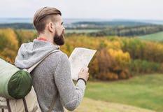 Jonge mensenreiziger die zich bovenop de heuvel bevinden en aan de kaart kijken reis concept royalty-vrije stock afbeeldingen