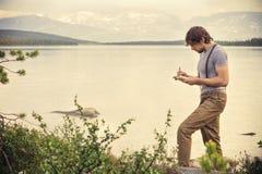 Jonge Mensenreiziger met het boek van de rugzaklezing Stock Afbeelding