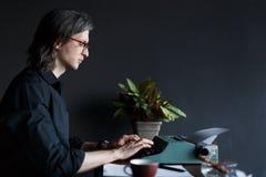 Jonge mensenschrijver in zwart overhemd met lang haar, in glazen die op een oude schrijfmachine op een lijst in zijn bureau typen royalty-vrije stock afbeelding