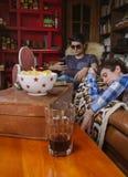 Jonge mensenslaap bij bank en vrienden het kijken Stock Foto