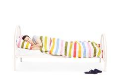 Jonge mensenslaap in een comfortabel bed Stock Afbeelding