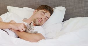 Jonge mensenslaap op de kat van de bedholding in zijn wapens 4K 4k stock videobeelden