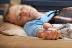 Jonge mensenslaap op de laag met een fles royalty-vrije stock fotografie