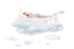 Jonge mensenslaap op een comfortabel bed in wolken royalty-vrije stock foto's