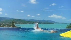 Jonge mensenslaap op gele matras en het vallen in turkoois water zwembad stock videobeelden