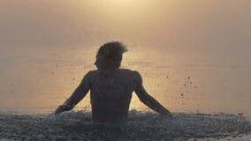 Jonge mensensprongen uit een meer met een het schudden hoofd in slo-mo stock footage