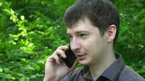 Jonge mensenvraag die cel slimme telefoon met behulp van die in openlucht knappe kerel sprekende close-up over groene bomen langz stock videobeelden