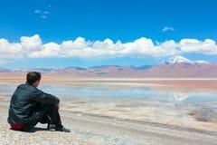 De zitting van de mens op de kust van meer Royalty-vrije Stock Foto