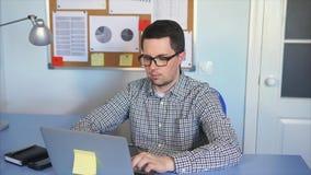 Jonge mensenzitting bij bureau in bureau, die aan laptop computer werken stock video