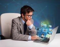 Jonge mensenzitting bij bureau en het letten van op zijn fotoalbum op lapt Royalty-vrije Stock Afbeeldingen