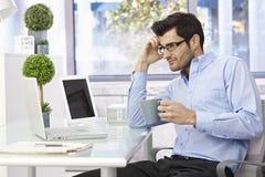 Jonge mensenzitting bij bureau het werken Stock Afbeelding