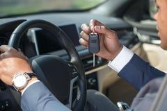 Jonge mensenzitting binnen auto met het zeer belangrijke close-up van het holdingsstuurwiel royalty-vrije stock fotografie