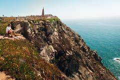 Jonge mensenzitting die alleen en in de Atlantische Oceaan op de rotsen van Cabo bekijken DA Roca, Portugal Stock Foto's