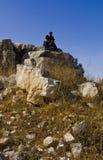 Jonge mensenzitting die op kalksteenrots een kanon houdt Royalty-vrije Stock Foto