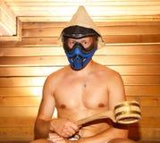 Jonge mensenzitting in Fins bad in paintballmasker Stock Fotografie