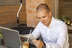 Jonge mensenzitting, lezing de krant en het drinken koffie stock foto