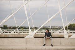 Jonge mensenzitting op de moderne brug in de stad, die zijn smartphone gebruiken Royalty-vrije Stock Afbeelding