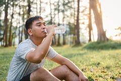 Jonge mensenzitting op de tuin en het drinkwater na het lopen stock foto's