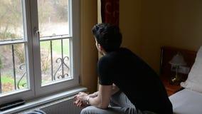 Jonge mensenzitting op droevig of ongerust gemaakt bed, het denken stock videobeelden
