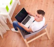 Jonge mensenzitting op stoel met laptop Stock Foto