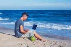 Jonge mensenzitting op strand met laptop stock foto