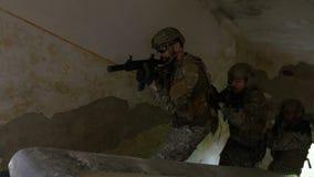 Jonge militairen op een opdracht om terroristen te doden die op treden aan parterre van een geruïneerd gebouw op zoek naar de doe stock footage