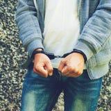 Jonge misdadige status in handcuffs, in openlucht Concept misdaad royalty-vrije stock fotografie